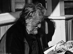 Current events. (Neil. Moralee) Tags: neilmoralee man face portrait profile news paper reading events old mature wrinkled age elderly shadow bright sunlight sunshine hair black white bw bandw blackandwhite mono monochrome neil moralee olympus omd em5 street uk watched