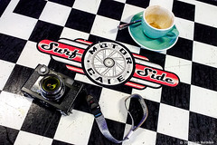 camera and coffee  #140429021 (lynnb's snaps) Tags: motog3 surfsidemotorcafe cafe cameraandcoffee cellphones colour digital table check pattern cup coffee camera graphic 2019 sydney australia leicacl
