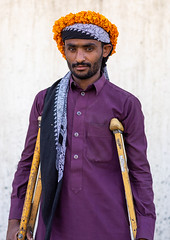 Portrait of a yemeni refugee with crutches wearing a floral crown on the head, Jizan Province, Addayer, Saudi Arabia (Eric Lafforgue) Tags: addayer adult arabia colorimage crutch cultures decoration ethnography floralgarland flower flowercrown flowers indigenousculture jizanprovince ksa lookingatcamera males man marigold men middleeast middleeastern oneadultonly onemanonly oneperson orange photography plant portrait refugee saudiarabia saudi181943 tihama tradition travel tribal tribe vertical war wounded yemeni sa
