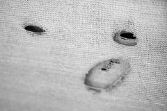 Sloth (belleshaw) Tags: blackandwhite downtownriverside fence holes fabric mesh obsession face eyes funny expression worn damage decay mouth texture detail abstract