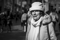 Keeping The Heat In (Leanne Boulton) Tags: urban street candid portrait portraiture streetphotography candidstreetphotography candidportrait streetportrait eyecontact candideyecontact streetlife old elderly woman female lady face eyes expression mood feeling emotion hat winter cold sunlight tone texture detail depthoffield bokeh naturallight outdoor light shade shadow city scene human life living humanity society culture lifestyle people canon canon5dmkiii 70mm ef2470mmf28liiusm black white blackwhite bw mono blackandwhite monochrome glasgow scotland uk