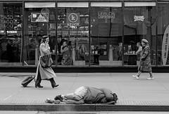 Striding By - 34th Street, NYC (TravelsWithDan) Tags: streetphotography blackandwhite bw monochrome nyc newyork manhattan 34thstreet candid women restaurant homeless asleep sidewalk street canong3x city urban people outdoors winter
