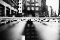 Grate (ewitsoe) Tags: monochrome ground view perspective bnw blackandwhite warsaw warszawa winter reflection city cityscape buildings blur poland erikwitsoe ewitsoe mood rain water canon