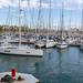 Paar fährt mit Segelboot in den Hafen Port Vell an der Promenade Rambla de Mar ein, in Barcelona (Spanien)