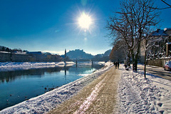 A wonderfully crisp winter day in Salzburg (echumachenco) Tags: sky blue sun winter january snow river water reflection tree path road city castle fortress festung hohensalzburg salzburg elisabethkai salzach austria österreich nikond3100 cloud building