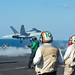 Sailors observe an F/A-18E Super Hornet launch from the flight deck of USS John C. Stennis