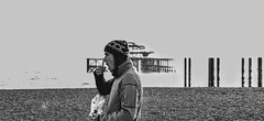 Brighton Man (Henry Hemming) Tags: man person walking eating chips brighton mono bw blackandwhite pier westpier beach contrast highcontrast