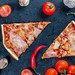 Two slices of homemade pizza on a black background with vegetables. Top view