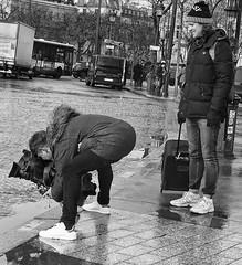 Strange Way To Take A Selfie (tcees) Tags: placecharlesdegaulle paris france avenuedefriedland x100 fujifilm finepix urban streetphotography street bw mono monochrome blackandwhite man woman people lamppost camera cobbles traffic road car bus van wet rain bag pavement sidewalk suitcase professionalvideocamera televisioncamera bend bent