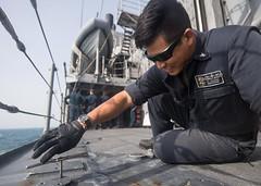 U.S. Navy Gunner's Mate 3rd Class Daniel Zhang, from Houston, tightens a bolt aboard USS Mobile Bay (SurfaceWarriors) Tags: guidedmissilecruiser ussmobilebaycg53 ticonderogaclass usn csg3 arabiangulf us