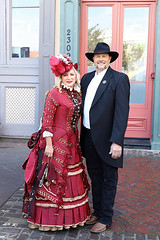 Beautiful Lady and a Texas Ranger (wyojones) Tags: texas galveston dickensonthestrand holidayfestival hat dress blond hair girl lady lovely woman beautiful beauty feathers smile pretty curls lace red man gentleman lawman texasranger boots suit beard badge