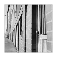 Door for the Block (Thomas Listl) Tags: thomaslistl blackandwhite biancoenegro noiretblanc monochrome grey filmphotography film analog yashicamat124g yashica mediumformat 6x6 square architecture urban city topography mundane door wall bricks kodak trix kodaktrix 120