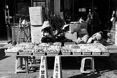 Hide and seek (Go-tea 郭天) Tags: qingdao huangdao shandong winter cold sun sunny shadow hide hidden coat cap mess messy business shop sale saler seat seated alone lonely woman busy duty mobile phone cell cellular cellphone table street urban city outside outdoor people candid bw bnw black white blackwhite blackandwhite monochrome naturallight natural light asia asian china chinese canon eos 100d 24mm prime