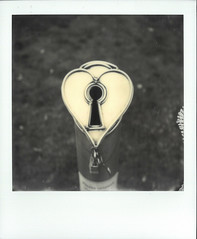 Key To The Heart (gooey_lewy) Tags: vancouver lovers statue padlock art display interactive canada key heart polaroid sx70 instant film photo photography sx 70 road sky black white mono b w love