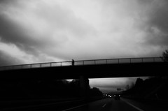 Man on a bridge (stefankamert) Tags: street bridge lines man blur blurry mysterious clouds sky black noiretblanc noir blackandwhite blackwhite grain ricoh gr ricohgr grii 28mm stefankamert nopostprocessing