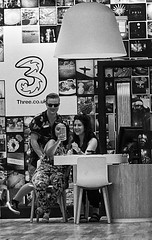 Twos Company..... (tcees) Tags: cabotcircus southstreet bristol x100 fujifilm finepix bw mono monochrome blackandwhite urban streetphotography street man woman people shops mobilephone selfie chair lampshade shop floor 3 pictures desk pose uk