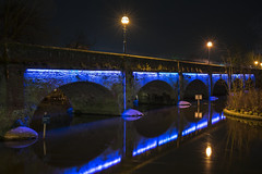 Tramway Bridge #1 (John Joslin) Tags: bridge streetlight streetlamp stratforduponavon stratford canal water longexposure river avon walkway lamps tramway evening night footbridge architecture arches led england winter blue a7rii branches trees colour color dark dusk landscape outdoors outside reflections reflection sony zeiss 50mm