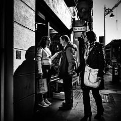 Networking (Kieron Ellis) Tags: people man woman talking jesture window sign streetlamp crane bag bin candid street blackandwhite blackwhite monochrome