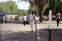76-229 (ndpa / s. lundeen, archivist) Tags: nick dewolf color photograph by 1976 1970s film 35mm 76 reel76 early1976 africa northernafrica northeastafrica sudan thesudan african sudanese khartoum city town candid streetphotography streetlife citylife people street cars vehicles automobiles traffic parkedcars sidewalk pedestrian pedestrians headcovering dress woman youngwoman man men youngman youngmen trafficsign curb motorbike motorcycle scooter truck tob hijab tobe