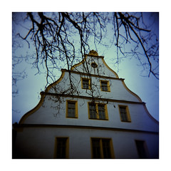 Ehehaltenhaus (Armin Fuchs) Tags: arminfuchs würzburg lavillelaplusdangereuse holga velvia100 120mm 6x6 ehehaltenhaus square analog film mediumformat mittelformat blue house branches sky yellow windows tree winter lensblur vignette fujichrome