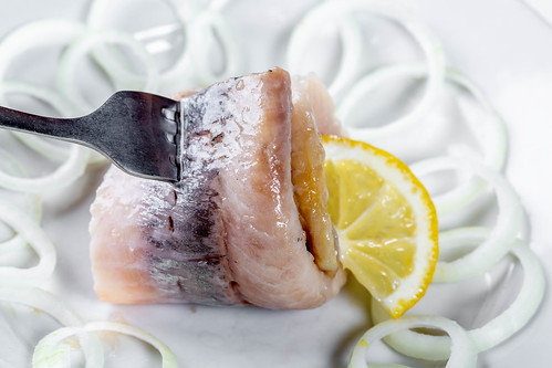 Herring with sliced onion and lemon on white ceramic plate