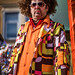 Man at carnival with a Disco Stu hair style and colorful outfit