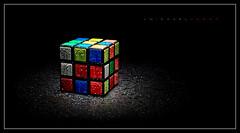 Wet Cube (J Michael Hamon) Tags: rubik rubikscube cube square colors wet water drops droplets splash light lighting photoborder blackbackground hamon nikon d7100 nikkor 35mm stilllife object tabletop toy