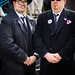 Two men at carnival dressed as mafia bouncers