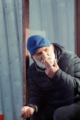 Turkish man outside the New Mosque (AnniversaryRoad) Tags: 135 35mm 400 400asa 400iso 400h 90mm asia constantinople elmarit eminonu europe fatih fuji400h istanbul leica leicam6 leitz m6 middleeast turk turkey turkish analog analogphotography analogue color colour film filmgrain filmphotography fuji fujifilm man outdoor outside people person portrait rangefinder smoking street streetphotography streetportrait
