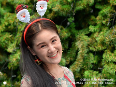 2018-12a Jingle-belling in Bangkok (09) (Matt Hahnewald) Tags: matthahnewaldphotography facingtheworld people head tiltedhead face eyes smilingeyes mouth teeth bell earrings expression lookingatcamera smile highspirits longhair partinghair christmas headband santaclaus tree consent fun concept humanity living culture tradition enjoyment happiness joy humor optimism traditional cultural celebration bangkok thailand asia asian thai southeastasian individual oneperson female young woman photo detail background nikond610 nikkorafs85mmf18g 85mm 4x3ratio resized 1200x900pixels horizontal street portrait closeup headshot seveneighthsview outdoor colour posing smiling happy cheerful joyous clarity