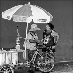 Minnie (John Riper) Tags: johnriper street photography straatfotografie square vierkant bw black white zwartwit mono monochrome john riper fuji fujifilm xt2 xf 18135 rio riodejaneiro brazil conversation chat woman lady man dress shirt minnie mouse orange press stall bike delivery carrier trike tricycle cycle parasol sunshade supergasbras
