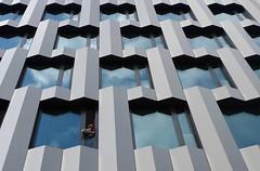 Man at work (Tjaldur66) Tags: architecture modernarchitecture facade tradesman windows clouds reflection officebuilding city lines zurich switzerland working building geometry