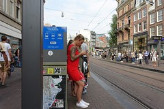 Waiting for the tram (theo_vermeulen) Tags: amsterdam tram tramstop red candid street tattoo phone
