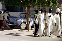76-093 (ndpa / s. lundeen, archivist) Tags: nick dewolf nickdewolf color photographbynickdewolf 1976 1970s film 35mm 76 reel76 early1976 africa northernafrica northeastafrica sudan thesudan african sudanese people streetlife citylife streetphotography unidentifiedcity men robes whiterobes clothing whiteclothing robe whiterobe turban turbans headcovering headcoverings city town street pedestrians car cars vehicle vehicles automobile automobiles parkedcars tree trafficsign khartoum jalabiya