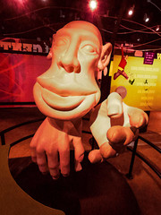 Hi There (Steve Taylor (Photography)) Tags: jumping happy hand head face digitalart model poster billboard orange red yellow brown smiling smile strange odd plastic railing cool calm man singapore asia sciencecentre