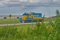 Port Manatee, Switcher, Route 24, Manatee, Florida (2 of 2) (gg1electrice60) Tags: portmanateeswitcher portmanatee portswitcher tampabay gulfofmexico us41 usroute41 electromotivedivision emd generalmotors gm gp10 roadnumber7972 diesellocomotive dieselengine portmanateenumber7972 portmanateeno7972 portmanatee7972 csxrailroad csx csxt freight locomotive yellowblue blueandyellow palmetto export import manateeharborchannel manateecountyportauthority foreigntradezone switcher railroadyard railyard rryard manateecounty florida fl unitedstates usa us america blueyellow yellowandblue restrictedarea fence cyclonefence brush trees grass weeds twowaysign 2waysign trafficsign