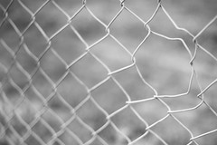 Pass Through (belleshaw) Tags: blackandwhite hemet fence chainlink damage bent metal hole stretched deformed detail abstract mesh obsession