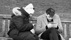 Texting one another (byronv2) Tags: street peoplewatching candid edinburgh edimbourg scotland blackandwhite blackwhite bw monochrome man woman phone cellphone texting mobilephone sitting seat seated bench banc park princesstreet princesstreetgardens newtown