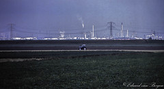 En de boer, hij ploegde voort . . (Eduard van Bergen) Tags: pernis botlek europoort europort maasvlakte industrie industrial estate moloch eaten eating feeding life live living chemical pipes chimneys schoorstenen tanks oil plants fabrieken raffinaderijen refineries man hubbie farm land farmland farmer field birds genesis trekker tractor plow plowing hoeksewaard goudswaard rotterdam dervaderenerf away hydro power powerlines eggen ploegen factories gone future food expanding chemistry akker teelt people