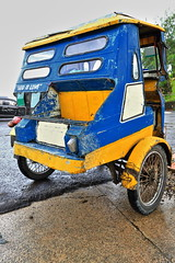 Colorist tricycle at the Chocolate Hills Complex parkng lot. Carmen-Bohol island-Philippines-0611 (rweisswald) Tags: motortricycle publictransportation roofedmotorbike enclosedmotorcycle sidecar autorickshaw publicutility taxinumber forhire passengertricycle trike coveredvehicle colorful colorist manycolored motley bluepainted red yellow green metal metallicframe structure cockpit wheel windshield seat rearviewmirror handlebar mudguard tire exhaustpipe headlight parked stopped outofservice notworking road street wet rain shower sidewalk parkinglot godislove chocolatehillscomplex carmenmunicipality boholisland centralvisayas philippines