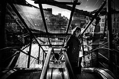 Escalier en verre (Kieron Ellis) Tags: woman escalator glass windows buildings traffic cars city bright reflections contrast rising sky cloud glasses candid street blackandwhite blackwhite monochrome