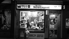 Newsagent At Night (byronv2) Tags: edinburgh edimbourg edinburghbynight night nuit nacht blackandwhite blackwhite bw monochrome window peoplewatching candid street dalry dalryroad haymarket shop newsagent store