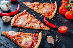 Three slices of pizza with bacon and tomato sauce with spices on a black background (wuestenigel) Tags: nutrient lay composition garlic sauce recipe pepper table eat background dinner delicious pizza homemade cooked meal cheese organic vegetable flat tomato wooden grey traditional gourmet italian bacon chili tasty meat food nutrition cherry ingredient healthy cuisine top slice black space fresh spices view appetizing