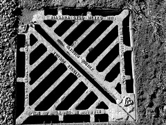 manhole cover (Jackal1) Tags: manholecover metal blackwhite bw words niagara lines abstract street draincover monochrome