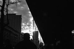 Figure formed by two rays (ewitsoe) Tags: city ewitsoe street warszawa winter erikwitsoecom poland urban warsaw blackandwhite mono monochrome sunset evening silhouette building 35mm nikond80 walking pedestrians