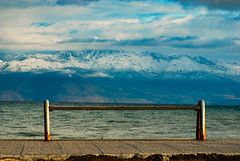 A winter view (jimiliop) Tags: rusty bench sea mountains view winter snow silence clouds sky blue morning