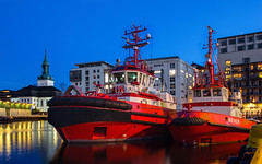 Midnight in the harbor (Siggi007) Tags: tugboat tugs boats night sky midnight evening lights light reflections colors colour farben blue red waterfront docks moored buildings church work living mood water sea seaside bergen norway norge norwegen ships tranquil yellow urban outdoors outdoor abend details dawn himmel longexposure le orange canon colores vessel nacht 60d