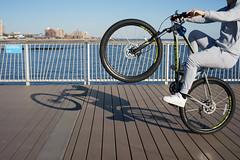 Wheelie (dtanist) Tags: nyc newyork newyorkcity new york city sony a7 konica hexanon brooklyn coney island steeplechase pier boardwalk sea bike bicycle bicyclist cyclist wheelie trick shadow faceless
