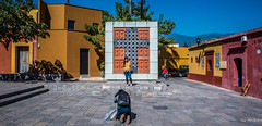 2018 - Mexico - Oaxaca - Plaza de la Cruz de Piedra (Ted's photos - Returns late Feb) Tags: 2018 cropped mexico nikon nikond750 nikonfx oaxaca tedmcgrath tedsphotos tedsphotosmexico vignetting plazadelacruzdepiedra oaxacaplazadelacruzdepiedra plazadelacruzdepiedraoaxaca photographer pose posing streetscene street plazadelacruzdepiedracross cross monument lacruzdepiedra lacruzdepiedraoaxaca thestonecross thestonecrossoaxaca oaxacathestonecross stonecross bluesky blue people peopleandpaths pathsandpeople shadow shadows backpack