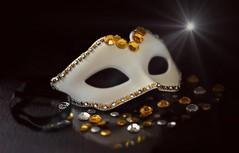 Bal Masqué (Through Serena's Lens) Tags: lookingcloseonfriday mask white gold closeup beads rhinestone dof reflection darkbackground tabletop stilllife canoneos6dmarkii